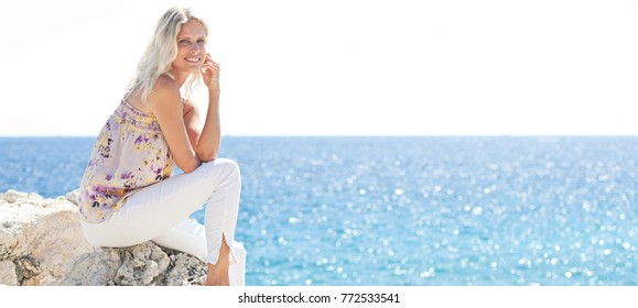 Panoramic of smiling beautiful blond woman sitting relaxing on cliff contemplating the sea on holiday destination, looking at camera outdoors. Healthy wellness travel recreation lifestyle, nature.