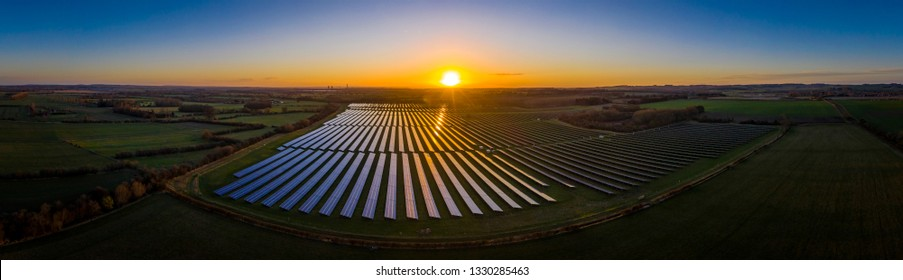 Panoramic of a solar farm at dawn taken from the air