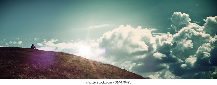 Panoramic of Solitary Person Sitting Alone on Hill Watching Bright Sunrise in Cloudy Blue Sky - Concept Image