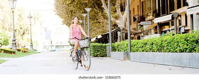 Panoramic spacious view of a young joyful woman riding a bicycle through a large avenue visiting a destination city on vacation during a sunny summer day, outdoors.