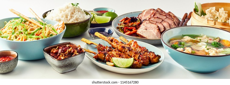 Panoramic Still Life View of Assortment of Chinese Asian Inspired Food Dishes in front of White Background