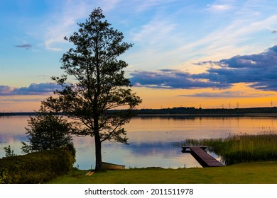 Panoramic summer sunset view of Jezioro Selmet Wielki lake landscape with vintage pier, reeds and wooded shoreline in Sedki village in Masuria region of Poland - Shutterstock ID 2011511978