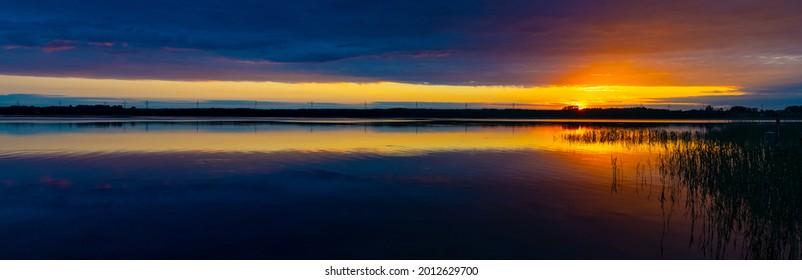 Panoramic summer sunset view of Jezioro Selmet Wielki lake landscape with colorful sky in Sedki village in Masuria region of Poland