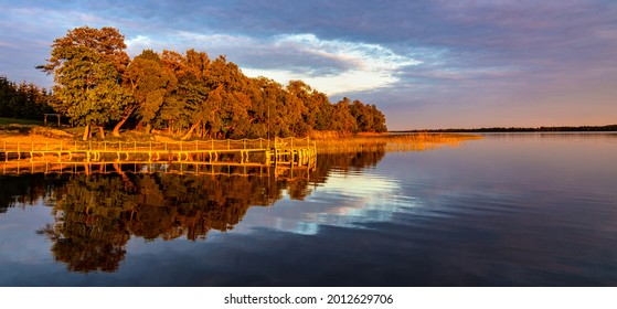 Panoramic summer sunset view of Jezioro Selmet Wielki lake landscape with vintage pier, reeds and wooded shoreline in Sedki village in Masuria region of Poland - Shutterstock ID 2012629706