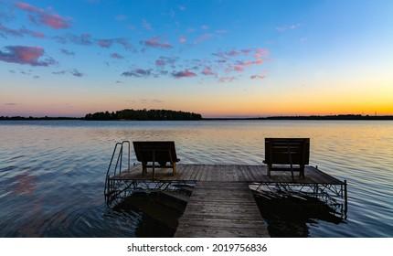 Panoramic summer sunset view of Jezioro Selmet Wielki lake landscape with recreation pier in Sedki village in Masuria region of Poland