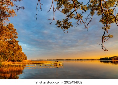 Panoramic summer sunset view of Jezioro Selmet Wielki lake landscape with vintage pier, reeds and wooded shoreline in Sedki village in Masuria region of Poland