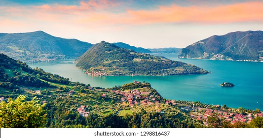 Panoramic summer view of Iseo lake. Impressive sunrise on Marone town with Monte Isola island, Province of Brescia, Italy, Europe. Traveling concept background.