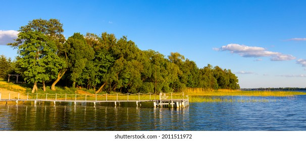 Panoramic summer view of Jezioro Selmet Wielki lake landscape with vintage pier reeds and wooded shoreline in Sedki village in Masuria region of Poland - Shutterstock ID 2011511972