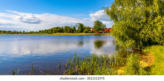 Panoramic summer view of Jezioro Selmet Wielki lake landscape with reeds and wooded shoreline in Sedki village in Masuria region of Poland - Shutterstock ID 2011511975