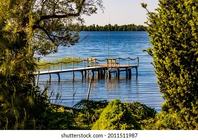 Panoramic summer view of Jezioro Selmet Wielki lake landscape with vintage pier reeds and wooded shoreline in Sedki village in Masuria region of Poland - Shutterstock ID 2011511987
