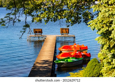 Panoramic summer view of Jezioro Selmet Wielki lake landscape with boat pier and wooded island in Sedki village in Masuria region of Poland - Shutterstock ID 2012629712