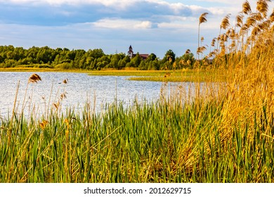 Panoramic summer view of Jezioro Selmet Wielki lake landscape with reeds and wooded shoreline in Sedki village in Masuria region of Poland - Shutterstock ID 2012629715