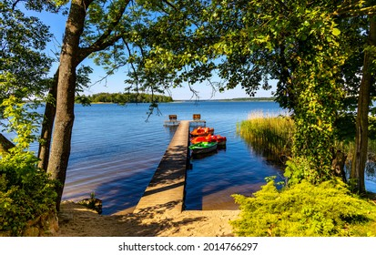 Panoramic summer view of Jezioro Selmet Wielki lake landscape with boat pier and wooded island in Sedki village in Masuria region of Poland - Shutterstock ID 2014766297