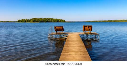 Panoramic summer view of Jezioro Selmet Wielki lake landscape with recreation pier in Sedki village in Masuria region of Poland - Shutterstock ID 2014766300