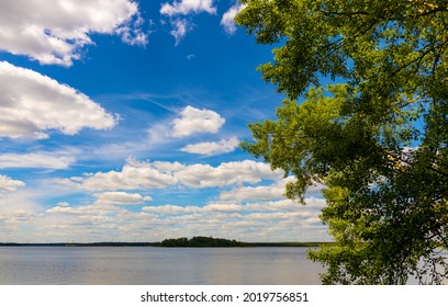 Panoramic summer view of Jezioro Selmet Wielki lake landscape with wooded island in Sedki village in Masuria region of Poland