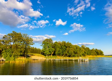 Panoramic summer view of Jezioro Selmet Wielki lake landscape with vintage pier reeds and wooded shoreline in Sedki village in Masuria region of Poland