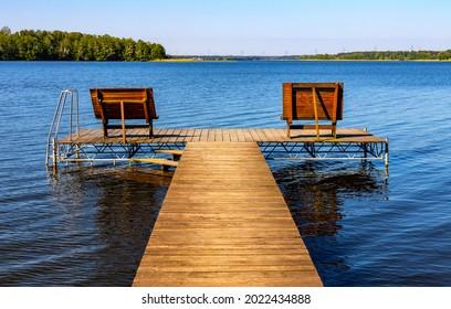 Panoramic summer view of Jezioro Selmet Wielki lake landscape with recreation pier in Sedki village in Masuria region of Poland