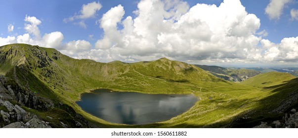 Panoramic summer's day view of Helvellyn horsehoe from Striding Edge (Lake District, Cumbria, England). A dozen walkers are visible on the ridge. Red Tarn is prominent, with Ullswater also visible.