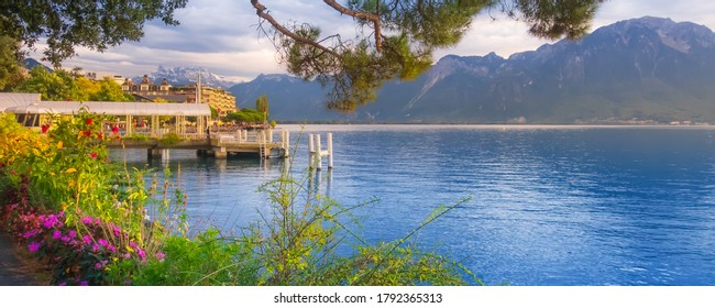 Panoramic sunset banner of Lake Geneva, Switzerland from Montreux promenade with colorful flowers, mountains behind