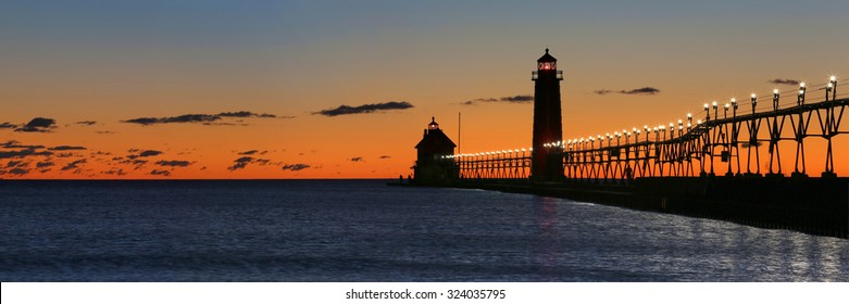 Panoramic of sunset at the Grand Haven South Pierhead Inner Light with Entrance Light in background in Grand Haven State Park in Grand Haven, Michigan