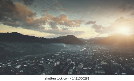 Panoramic Sunset Hill Suburban Town Aerial View. Mountain Cottage Village Scenery Overview. Countryside Settlement Overcast Sky. Clean Ecology Environmental Concept. Drone Fast Flight