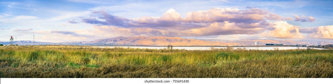 Panoramic sunset landscape of the marshes of south San Francisco bay, Mission Peak covered in sunset colored clouds in the background