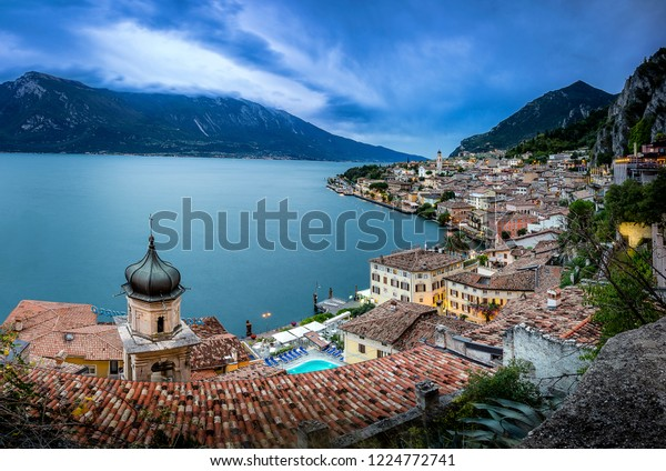 Panoramic sunset view of Limone Sul Garda, Italy from a viewpoint  above the town with the belltower of a church in front