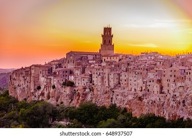 A panoramic sunset view of an old Tuscan town of Pitigliano -- the medieval city on the tuff cliffs with a belfry rising upon the red roofs. The bright sun is near the horizon in the orange sky.