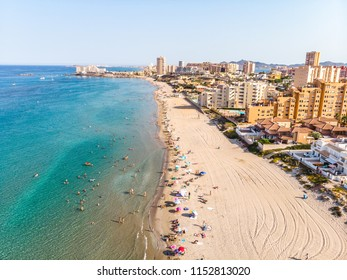 Panoramic sunset view on sandy arch of La Manga with its boat parking area and sand-bank La Manga, Cartagena, Murcia, Spain, Summer 2018 from drone People swiming and relaxing on the beach