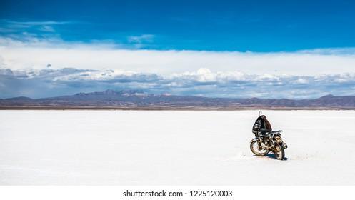 Panoramic sunshine scenery of Salar de Uyuni in Bolivia and motobike on the background of rocky mountains ridge