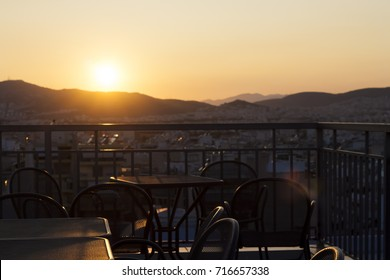 Panoramic terrace in Athens, Greece. Skyline sunset mountains view, railing, chairs and tables.  Blurred photo, selective focus, copyspace, perfect as background.
