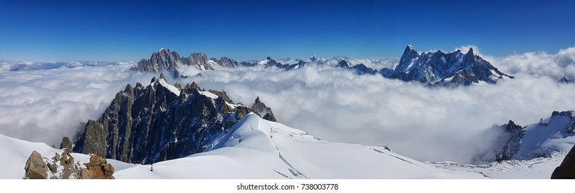 Panoramic top view of the Alps mountains covering with snow among the white clouds and blue sky in a sunny day. French Alps mountain. Chamonix Mont Blanc, France.