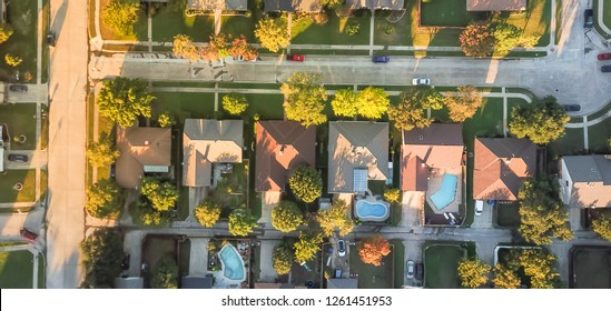 Panoramic top view residential neighborhood with cul-de-sac (dead-end) in Carrollton, Texas, USA in autumn sunset. Row of tightly packaged home with swimming pool, garden, driveway, attached garage