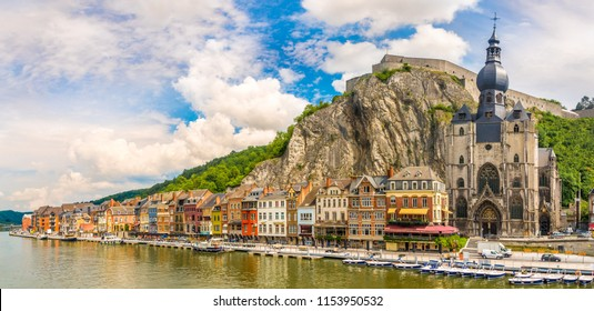 Panoramic vew at the embankment of Meuse river with houses and church of Our Lady Assumption in Dinant, Belgium