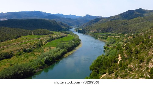 Panoramic view above Ebro River valley in Catalonia, Spain. Farm fields viewed from village of Miravet on sunny day.