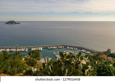 Panoramic view from above of the harbor with docked boats, the Cappelletta (little chapel) and the Gallinara Island, Alassio, Liguria, Italy