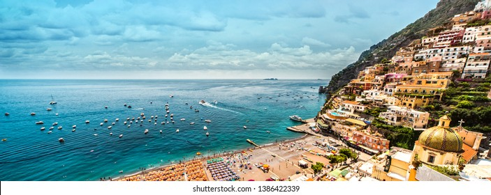 Panoramic view from above, hillside houses on the mountain, turquoise sea, beach full with sun umbrellas sunbed people tourists enjoy summer on the coast of popular Amalfi coast. Positano, Italy