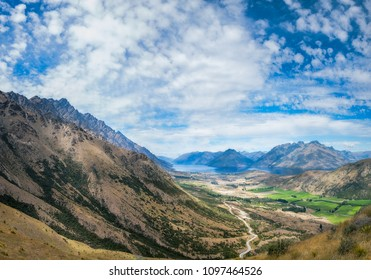 Panoramic View from above on the winding road from Queenstown to The Remarkables Ski Area showing spectacular mountain range and majestic mountain peaks with Lake Wakatipu in the distance.