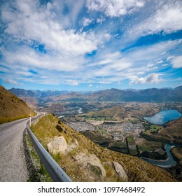 Panoramic View from above on the winding road from Queenstown to The Remarkable Ski Area showing the town bellow and Shotover and Kawarau rivers, Lake Hayes and spectacular mountain range behind.