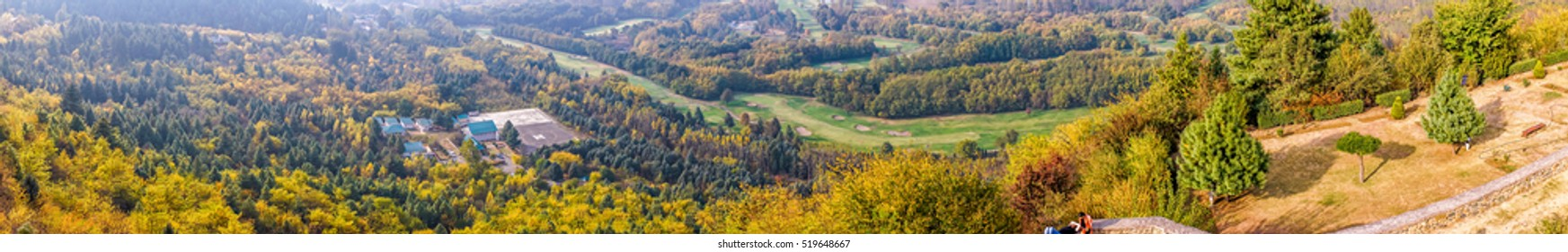 Panoramic view from above of park and hillside with autumn trees in Srinagar, Kashmir, India, in a blur background of a valley from afar