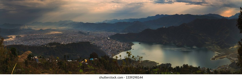 Panoramic view from above of Pokhara town and Pokhara lake side with the Himalayas mountain range in the background on a cloudy day. Taken from Sarangkot, Pokhara, Nepal - Image