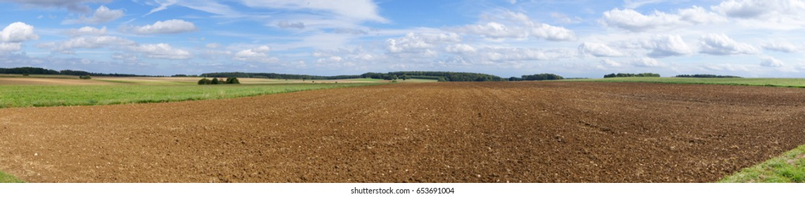 Panoramic view of agricultural landscape; Flat landscape with plowed field, meadows and wooded areas under cloudy blue sky; Wide field of view on North German flatland