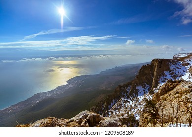 Panoramic view from Ai-Petri mountain to the sea, coast and city, Mishor, Crimea, Russia. The sun is reflected in the surface of the water, to the right is a fragment of a mountain with snow