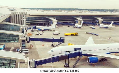 panoramic view of the airport operations, experts prepare the aircraft, trucks and tankers bringing up luggage and fuel, the passengers go to the aircraft in boarding bridge