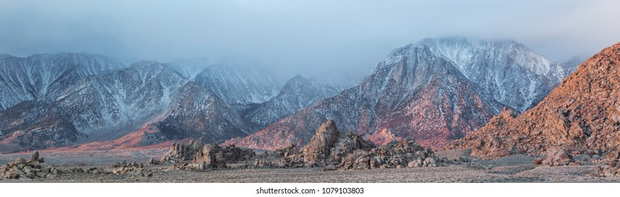 Panoramic view of Alabama Hills and eastern slopes of Sierra Nevada Mountains as dawn breaks casting soft pink light on cold blue mountains