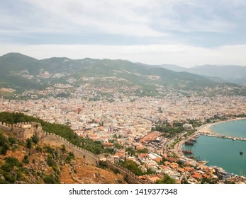 Panoramic view of Alanya, nautical vessels in the harbor, Alanya Castle fortress wall and mountains. Alanya, Antalya, Turkey