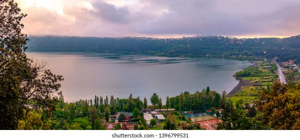 panoramic view of Albano Lake or Lago di Abano in the Roman Castle or Castelli Romani area near Rome in Lazio at sunset with purple sky .