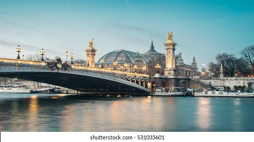 Panoramic view of the the Alexander III Bridge at dusk with Grand Palais (Great Palace) on the background. It's a deck arch bridge, regarded as the most ornate, extravagant bridge in the city.