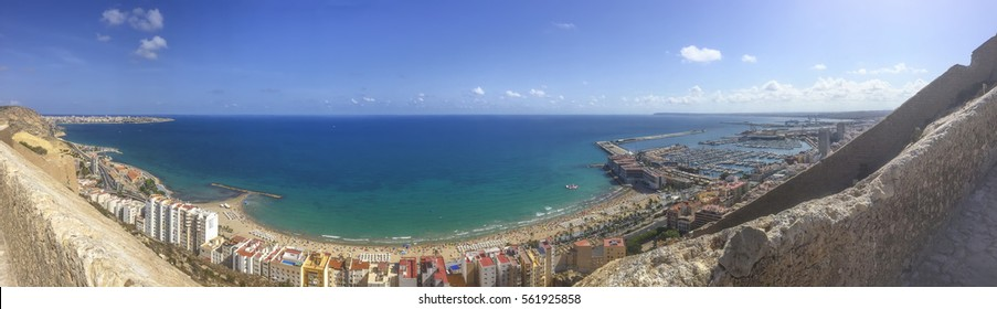 panoramic view of alicante coast line with buildings, harbour,  beach of postiguet and mediterranean sea taken from Santa Barbara castle