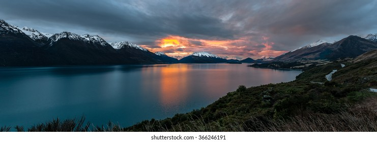 Panoramic view along the road from Queenstown to Glenorchy overlooking Lake Wakitipu and surrounding snow-capped mountains at sunset, New Zealand.